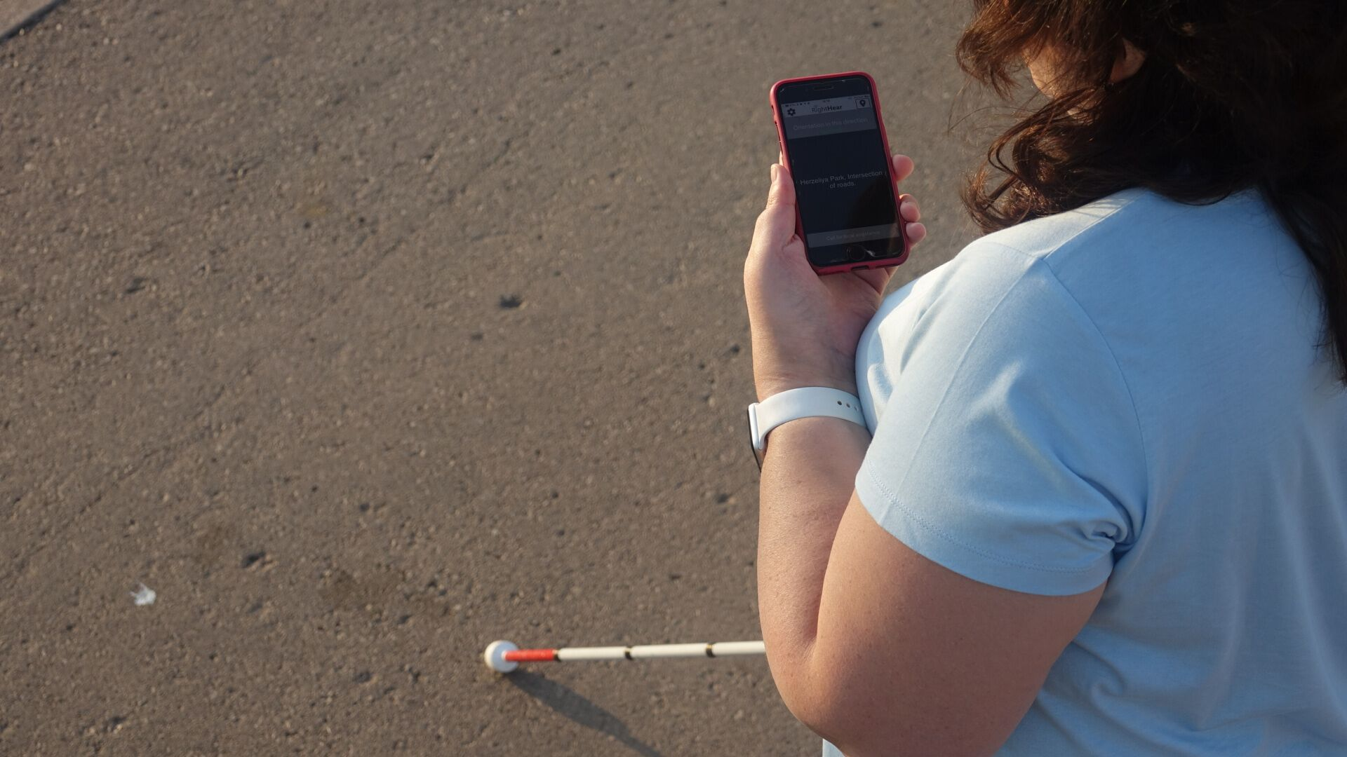 RightHear user with the app and cane