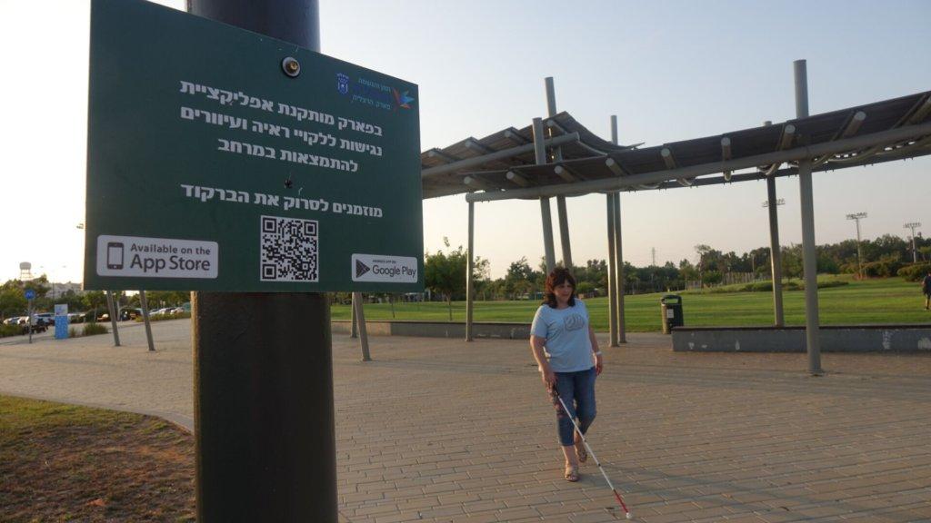 בתמונה: קרינה מצולמת ליד שלט בכניסה לפארק שמציין כי המקום נגיש באמצעות מערכת רייט-היר